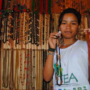 Priscila, de Jamaraquá, mostra orgulhosa alguns exemplares das peças de sementes e látex produzidas na comunidade.