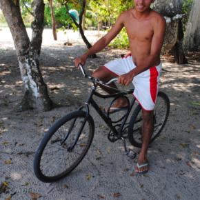 Para transitar pelas comunidades locais, o garoto usa uma bicicleta, como vários jovens da região